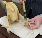 """Step 40 One strap loops over the end to become a """"hanging"""" loop. The other strap wraps around the handle to be a """"closure"""" strap. You should be able to slip it over the top of the handle. Tack both ends together using a dome head tack."""