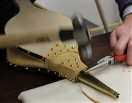 Step 42 Using flat head tacks, tack the brass nozzle to the nose. Tack it in 3 places – the top and each side.